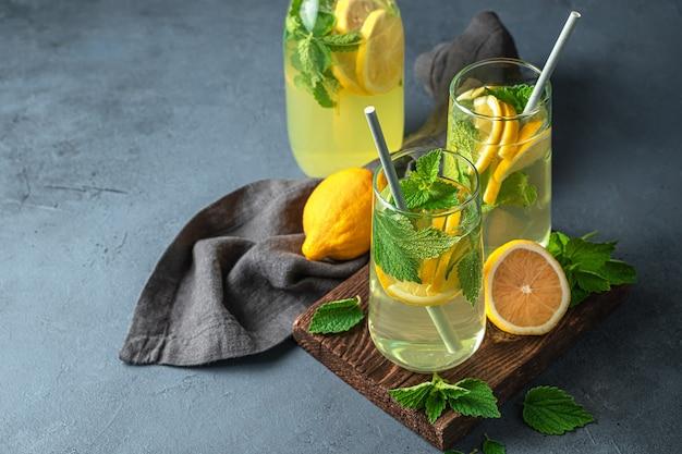 Летний, здоровый освежающий напиток на фоне графита. лимонад с лимонами и мятой. скопируйте пространство.