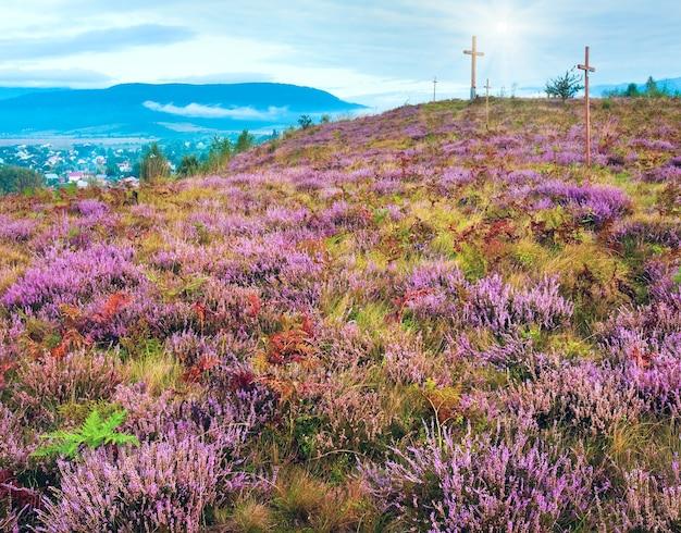 Летний холм с цветком вереска, вид на загородную местность туманным утром и деревянные кресты (львовская область, украина).