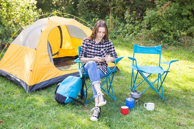 Summer, hike, tourism and nature concept - young woman sitting near tent