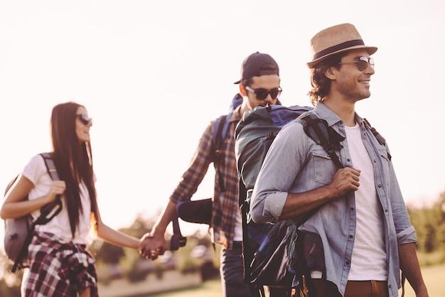 友達との夏のハイキング。一緒に歩いて幸せそうに見えるバックパックを持った若者