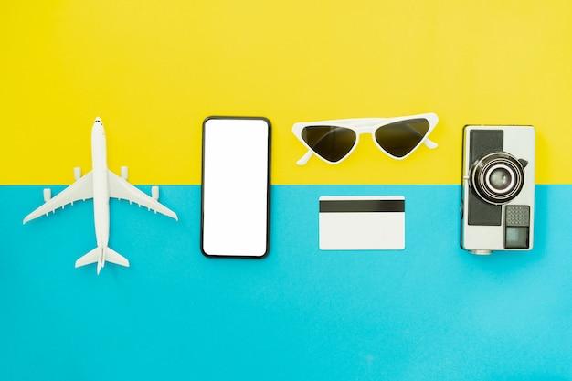 여름 휴가 및 여행 개념. 파란색 배경에 검은 스마트 폰 및 카메라와 안경의 상위 뷰.