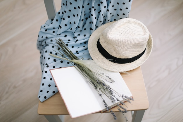 Летние каникулы и каникулы фон с синим платьем, соломенной шляпой, цветами и книгой