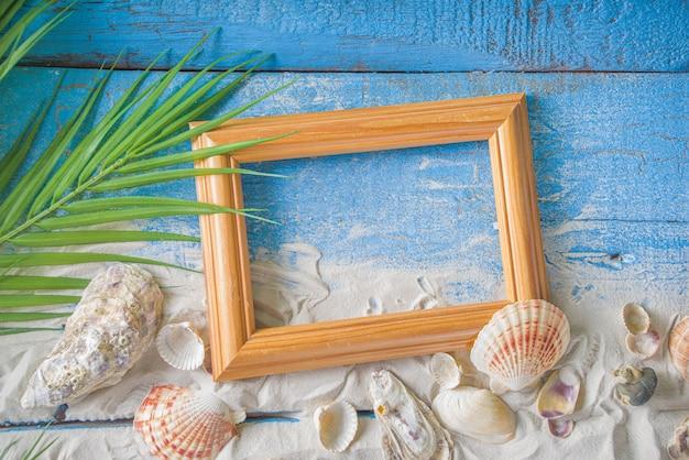 Летний праздник фон. старый синий деревянный стол с ракушками, морскими звездами и пляжным песком