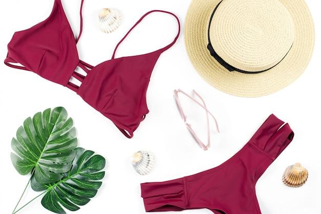 Летний праздник фон. концепция тропического лета с красным бикини, листья и ракушки на синем фоне.