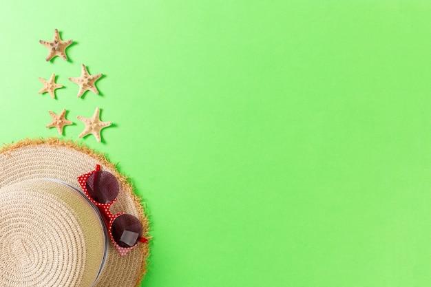 밀 짚 모자와 복사 공간 녹색 배경 평면도에 조개 여름 휴가 배경.