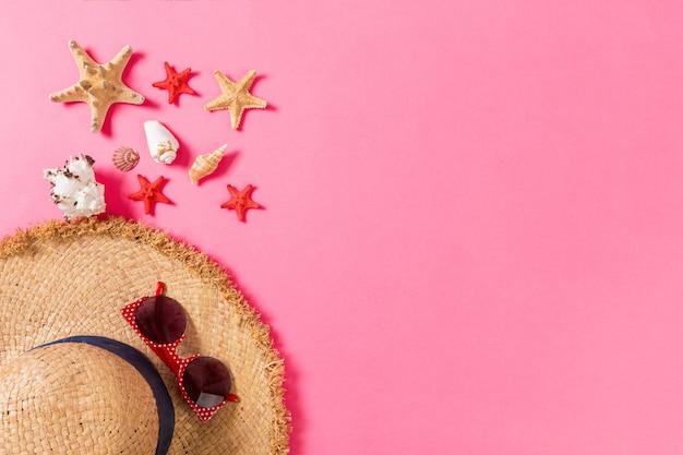 밀 짚 모자와 복사 공간 분홍색 배경 평면도에 조개 여름 휴가 배경.