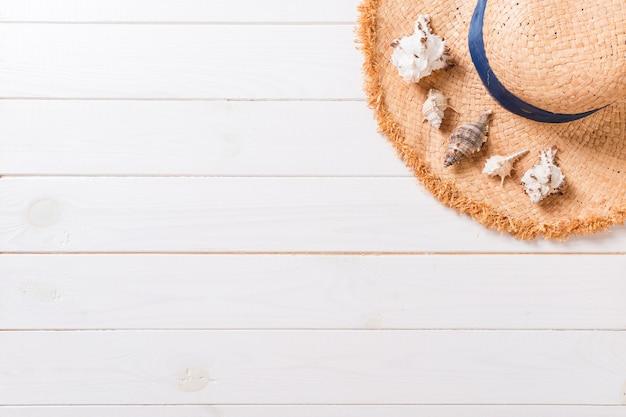 밀 짚 모자와 조개 복사 공간 나무 배경 평면도에 여름 휴가 배경.