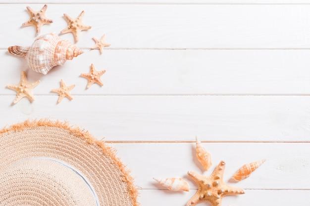 麦わら帽子とコピースペースを持つ木製の背景上面に貝殻の夏の休日背景