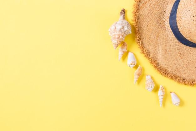 밀 짚 모자와 조개 복사 공간 노란색 배경 평면도에 여름 휴가 배경