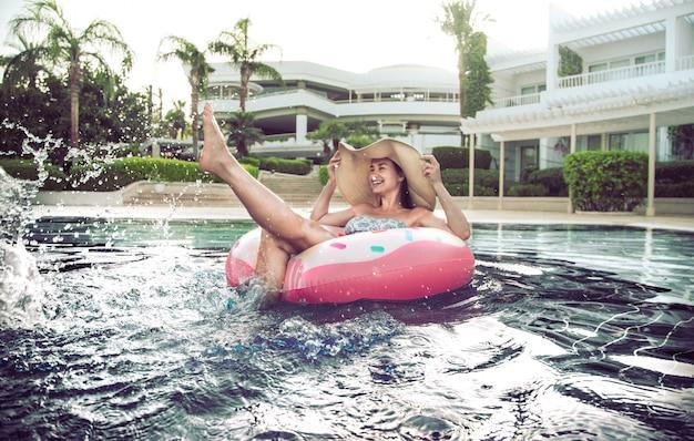 プールサイドの夏休み。女性はプールの膨脹可能なサークルでリラックスします。
