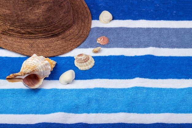 A summer holiday composition on a beach towel with seashells and a hat.