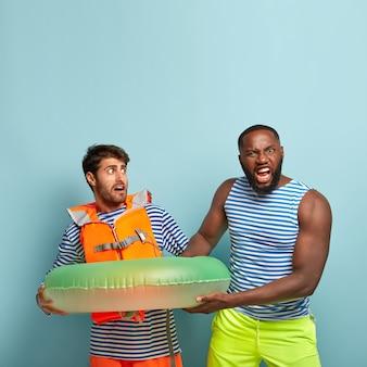 Концепция летнего отдыха. выстрел двух мужчин не может делить надутое плавательное кольцо. сердитый темнокожий мужчина требует у спасателя на пляже плавательного снаряжения