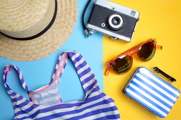 Summer holiday concept, travel concept with bag, camera and hat on blue and yellow background. flat lay