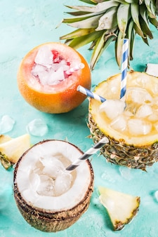 Summer holiday drink concept, set various tropical cocktails or juices in pineapple, grapefruit and coconut with ice, light blue concrete