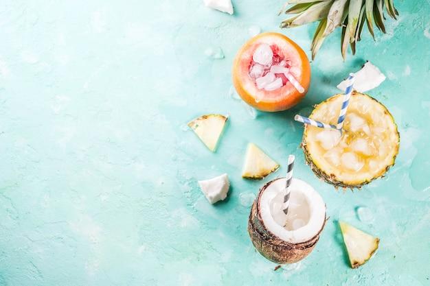 Концепция летнего отдыха, множество тропических коктейлей или соков в ананасе, грейпфруте и кокосе со льдом, голубым бетоном