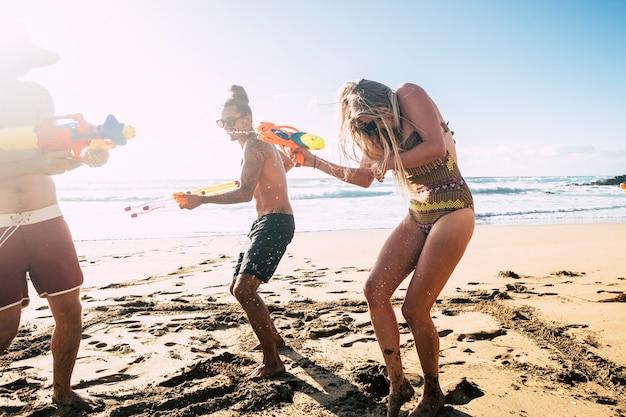 若い白人の友人のグループと夏休みの楽しい休暇の人々の概念は、海と空のシーンと砂の上のビーチで水鉄砲と一緒に遊ぶ