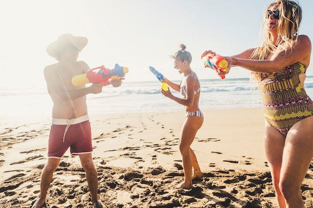 Summer holiday fun vacation people concept with group of young caucasian friends play together with water gun at the beach on the sand with ocean and sky scene
