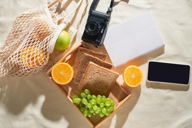 夏休み、ガジェット、果物、カメラ、明るい生地の背景にジュース。ピクニックのコンセプト。