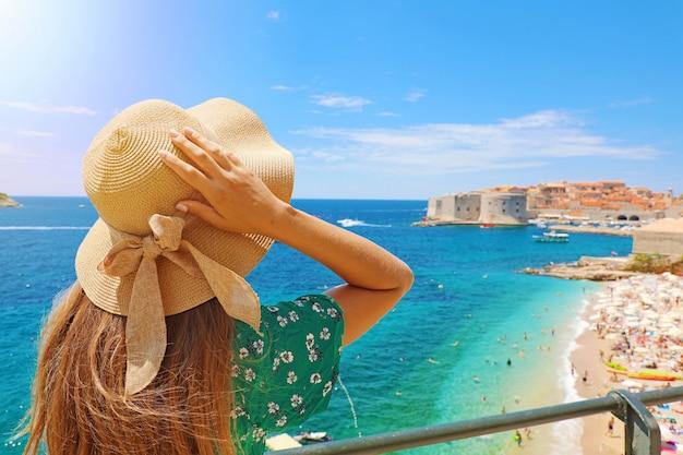 Летний отдых в хорватии. вид сзади молодой женщины, держащей ее шляпу с городом дубровник на заднем плане, хорватия, европа.