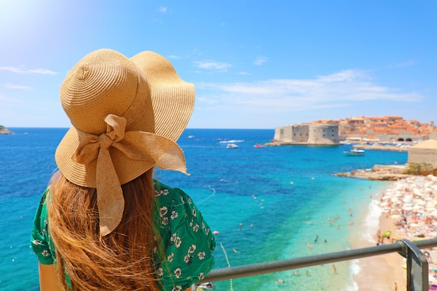 Летний отдых в хорватии. вид сзади молодой женщины с соломенной шляпой и зеленым платьем с старым городом дубровника на заднем плане, хорватия, европа.