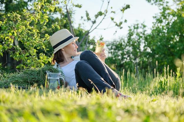 庭の夏休み、刈りたての草の上に座っている女性の庭師