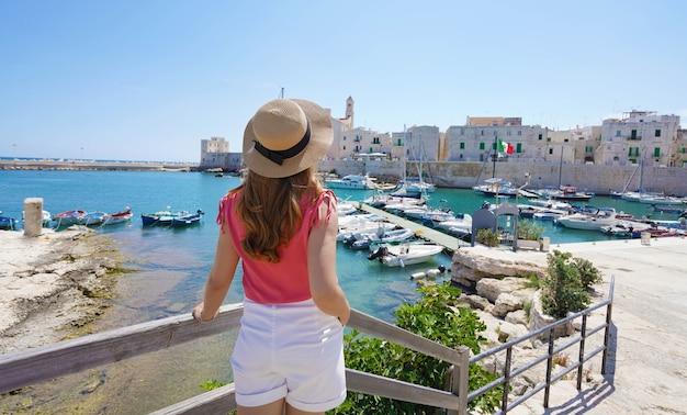 イタリアの夏休み。イタリア、ジョヴィナッツォ旧市街の若いスタイリッシュな女性の背面図。