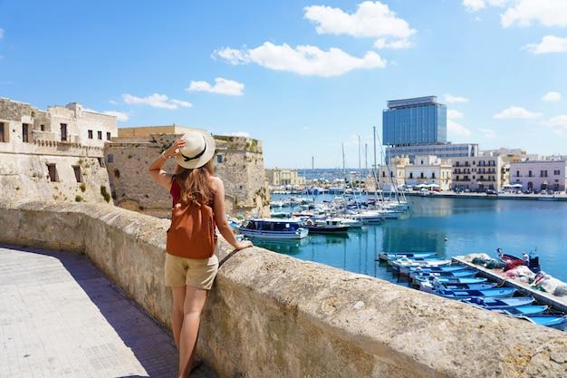イタリアの夏休み。ガリポリ旧市街、サレント、イタリアの帽子とバックパックを持つ若い女性の背面図。