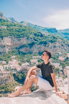 Summer holiday in italy. young man in positano village on the background, amalfi coast, italy