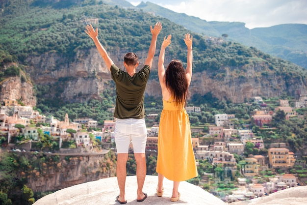 Summer holiday in italy. young man and woman in positano village on the background, amalfi coast, italy