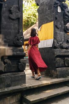 여름 휴가. 인도네시아 주민의 문화를 배우면서 불교 사원에 들어가는 기뻐하는 갈색 머리 여성