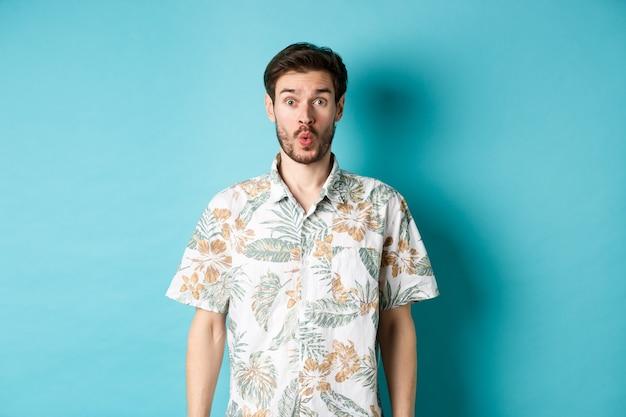 여름 휴가. 놀란 관광객은 와우라고 말하고 카메라를 쳐다보고 멋진 프로모션을 확인하고 파란색 배경에 하와이안 셔츠를 입고 서 있습니다.