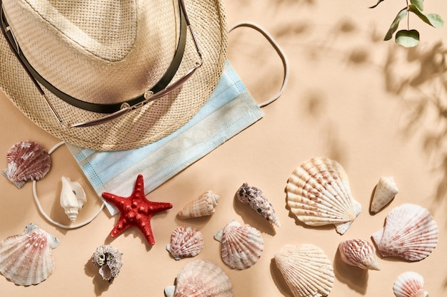 Summer holiday table. imitation of beach sand with seashell, starfish, mens straw hat, sunglasses and mask with deep shadows from the leaves and trees. sunny day. covid stop.top view.