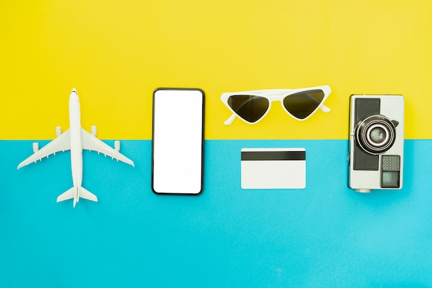 Summer holiday and travel concept. top view of black smartphone and glasses with camera on blue color background.