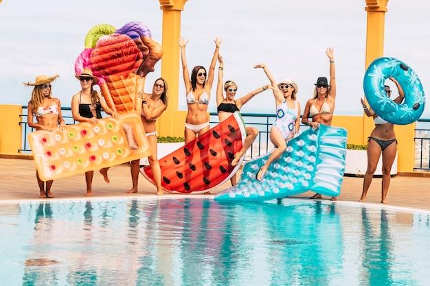 プールでの夏休み-旅行して若い美しい人々の友情を楽しむ-ビキニの女性のグループは色付きのトレンディなリロスインフレータブルを楽しんでいます-一緒に屋外を楽しんでいます