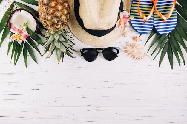 Summer holiday vacation concept. accessories for travel and exotic fruits on white wooden table. top view and flat lay