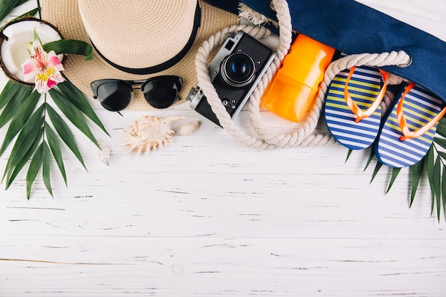 Summer holiday vacation concept. beach bag and accessories on white wooden table. top view and flat lay