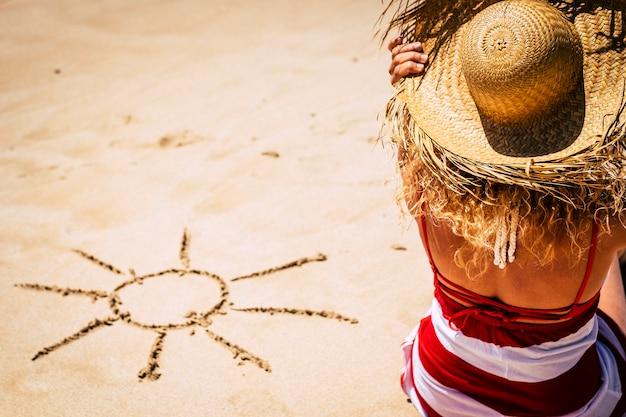 ビーチに座っている女の子と砂の上にdeisgned太陽と夏の休暇の休暇の概念