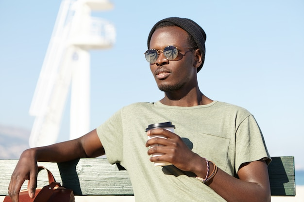 Summer, holiday and vacation. outdoor shot of relaxed carefree dark-skinned male tourist in eyewear and hat sitting on wooden bench