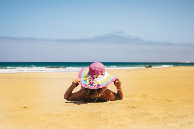 Summer holiday vacation and people relax at the beach concept with woman viewed from back have a sunbath on the sand with sea and blue sky in scene