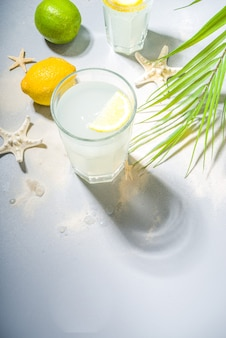 Summer holiday vacation tropical background with lemonade drinks. mojito cocktail with hard light and dark shadows, on a tropical background with starfish, palm leaves copy space for text