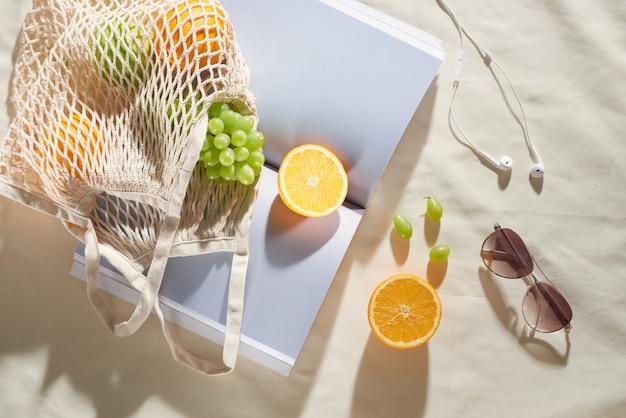 明るい背景にフルーツバッグ、メガネ、イヤホン、雑誌で夏休み。