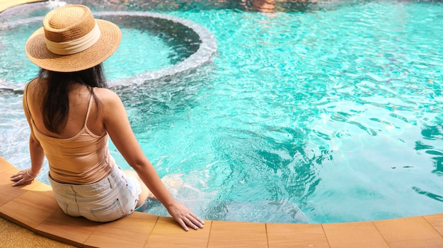 Summer holiday young asian beautiful woman relaxing in swimming pool at spa resort. beautiful tropical beach front hotel resort with swimming pool