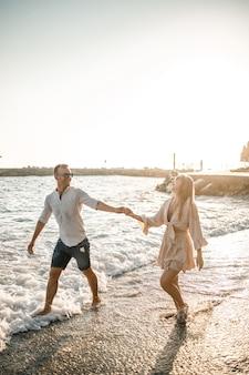 여름 휴가 및 여행. 해질녘 바다 물에 섹시 한 여자와 남자입니다. 사랑하는 부부는 일출 해변에서 휴식을 취합니다. 함께 여름날을 즐기는 부부의 사랑 관계. 선택적 초점