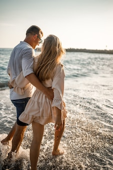 여름 방학 및 여행. 일몰 바다 물에 섹시 한 여자와 남자. 사랑하는 부부는 일출 해변에서 휴식. 여름날을 함께 즐기는 부부의 사랑 관계