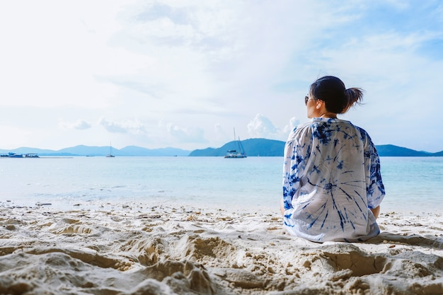 Летние каникулы и отпуск - вид сзади молодой женщины на пляже