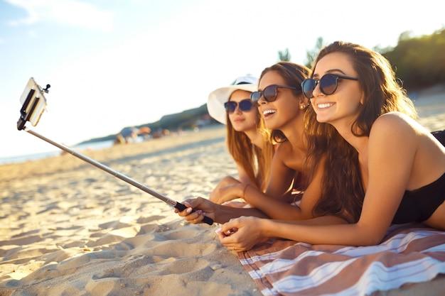 Летние каникулы и отпуск - девушки загорают на пляже. девушки делают селфи телефон. наслаждайтесь летним временем. веселье на пляже. отличное летнее настроение. солнечный день