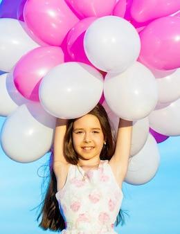 夏休み、お祝い、カラフルな風船を持つ子供たちの幸せな少女。幸せなティーンエイジャーまたはプレティーンの肖像画。子供の誕生日パーティー、祝う、休日。風船を持つ少女。