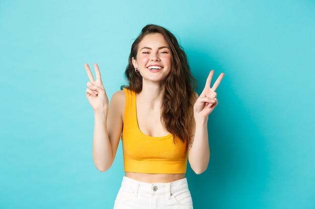 Vacanze estive ed emozioni concetto. felice bella ragazza che mostra segni di pace v e divertirsi, ridere e sorridere alla telecamera, in piedi su sfondo blu.