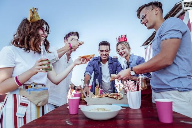 夏休み。彼女の友人にピザのかけらを与えている間、右手にボトルを持っている幸せな女性の人