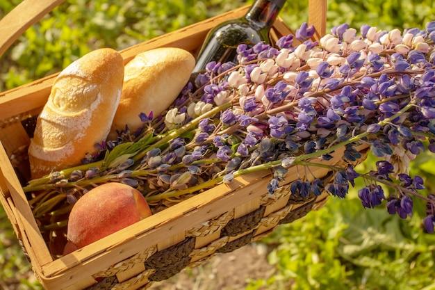 夏休み、アウトドアレクリエーション。花、食べ物、ワイン、夏のフルーツ、日当たりの良い背景のバスケット